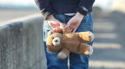 dramatic portrait of a little homeless boy holding a teddy bear, poverty, city, street
